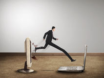Business man with long leg out from computer desktop to laptop Royalty Free Stock Photo