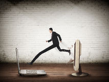 Business man with long leg out from computer desktop to laptop Royalty Free Stock Photos
