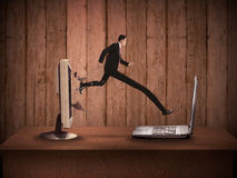 Business man with long leg out from computer desktop to laptop Stock Photos