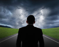 Business man look rainstorm clouds and lightning Royalty Free Stock Image