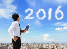 Business man look to 2016 cloud. Young business man using laptop and look to 2016 year text with blue sky and cloud and cityscape in the background, asian Royalty Free Stock Photos