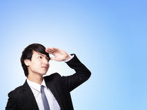 Business man looking away to copy space. Successful handsome business man purposefully looking away to empty copy space isolated on blue background, mode is a Stock Photos