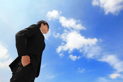 Business man looking away to copy space. Successful handsome business man purposefully looking away with blue sky, mode is a asian male Royalty Free Stock Photo
