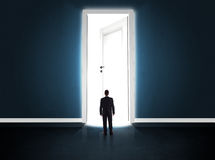Business man looking at big bright opened door Stock Photography
