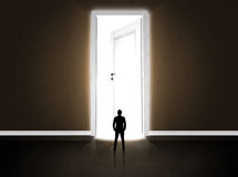 Business man looking at big bright opened door Royalty Free Stock Image