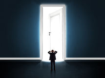 Business man looking at big bright opened door Royalty Free Stock Photography