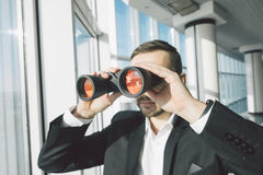 Business man looking with binoculars Stock Image