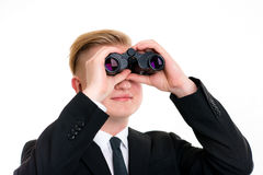 Business man is looking through binoculars. Young business man is looking through binoculars Stock Image