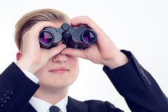 Business man is looking through binoculars. Young business man is looking through binoculars Royalty Free Stock Image