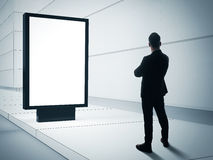 Business man looking at blank lightbox on the empty street Stock Image