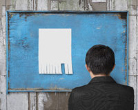 Business man looking at blank paper on old advertising billboard Royalty Free Stock Image