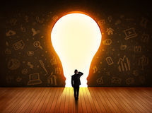 Business man looking at bright light bulb in the wall Royalty Free Stock Image