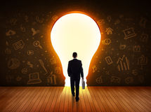 Business man looking at bright light bulb in the wall Stock Images