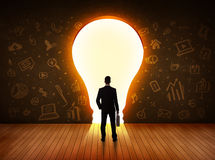 Business man looking at bright light bulb in the wall Royalty Free Stock Photos