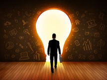 Business man looking at bright light bulb in the wall. Concept royalty free stock photography