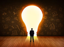 Business man looking at bright light bulb in the wall Stock Photography