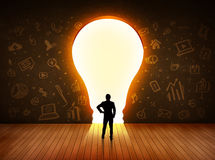 Business man looking at bright light bulb in the wall Stock Photos