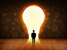 Business man looking at bright light bulb in the wall Royalty Free Stock Photography