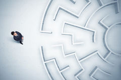 Business man looking at circular maze with nowhere to go Stock Photos