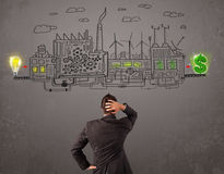Business man looking at factory that makes money from ideas. Concept Royalty Free Stock Images