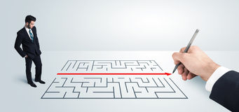 Business man looking at hand drawing solution for maze stock photography