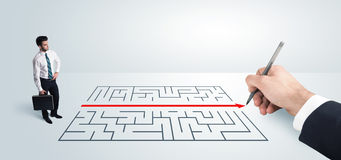 Business man looking at hand drawing solution for maze. Solution concept Stock Photos