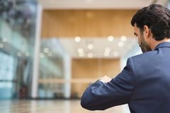 Business man looking at his clock against office background Royalty Free Stock Images