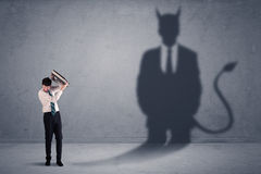Business man looking at his own devil demon shadow concept Stock Photography