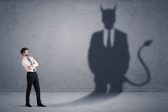 Business man looking at his own devil demon shadow concept Stock Images