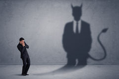 Business man looking at his own devil demon shadow concept Royalty Free Stock Photography