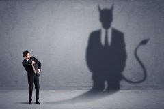 Business man looking at his own devil demon shadow concept. Background royalty free stock photography