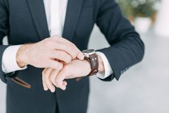 Business man looking at his watch. It`s time to do. Bright office interior, for business meetings royalty free stock photography