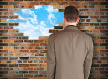 Business Man Looking at Hope Wall. A business man is facing a brick wall with a hole of clouds in it representing escape. Use it for a freedom or barrier concept stock image