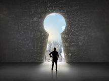 Business man looking at keyhole with bright cityscape concept. Background Royalty Free Stock Photography