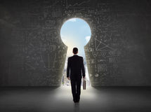 Business man looking at keyhole with bright cityscape concept Royalty Free Stock Photos