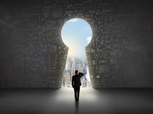 Business man looking at keyhole with bright cityscape concept. Background Royalty Free Stock Photos