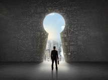 Business man looking at keyhole with bright cityscape concept. Background Stock Photo