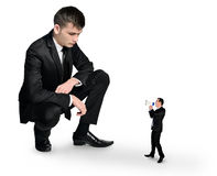 Business man looking at little man Royalty Free Stock Photography