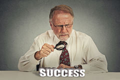 Business man looking through magnifying glass analyzing success Stock Photo