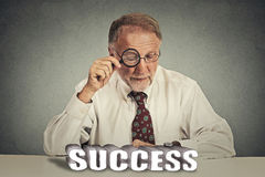 Business man looking through magnifying glass at success sign Stock Photo