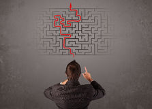 Business man looking at a maze and the way out stock illustration