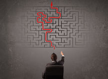 Business man looking at a maze and the way out. On brown wall Royalty Free Stock Images