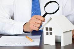 A business man looking at a model house holding a magnifying glass in his hand. stock photos