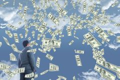 Business man looking at money rain against sky with clouds Stock Photos