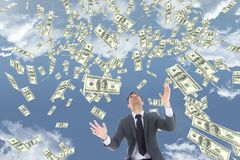 Business man looking at money rain against sky with clouds Royalty Free Stock Photo