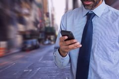 Business man looking at a phone against city background Stock Images