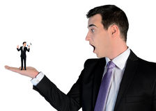 Business man looking shocked on little man Royalty Free Stock Photo