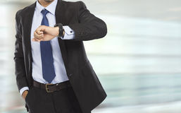 Business man looking at the time on his watch. Portrait of busy business man body looking at his watch in rush hour Royalty Free Stock Image