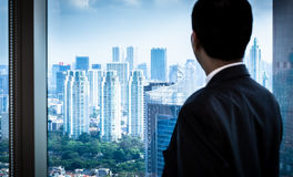 Business man looking to city skyline stock photography