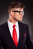 Business man looking to his side. Closeup picture of a young business man looking to his side, on dark background Stock Images